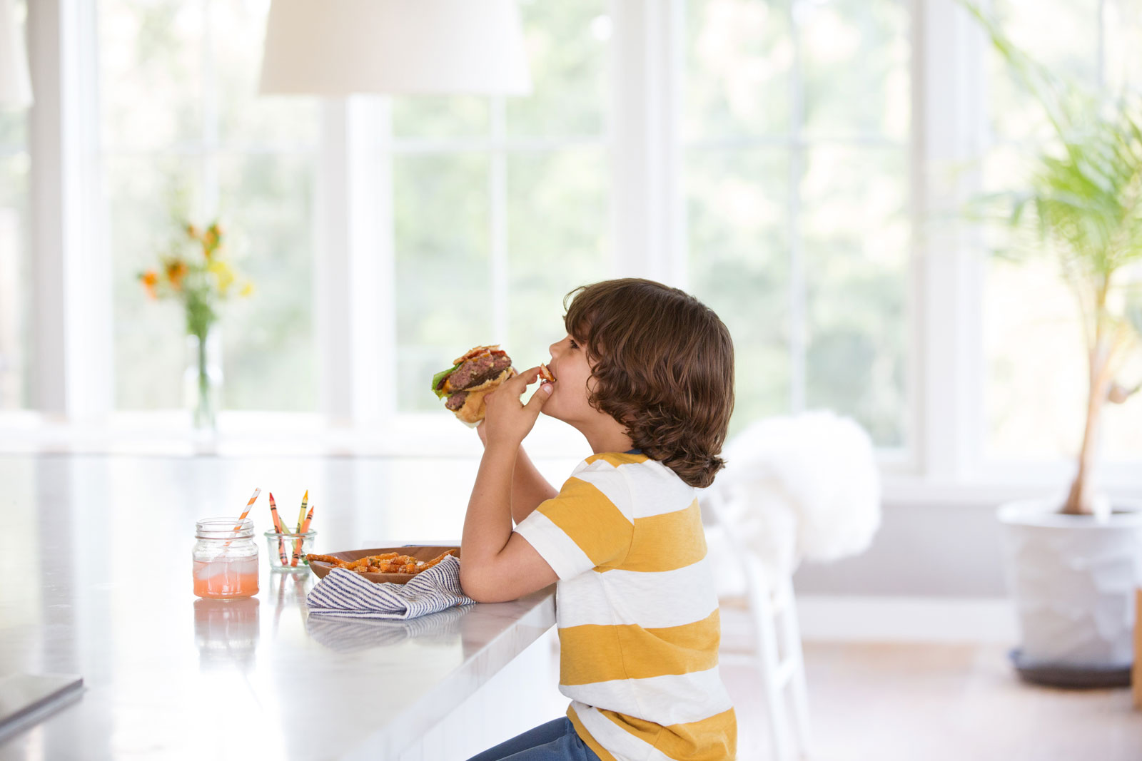 Boy at kitchen table eating a hamburger  | Dovis Bird Agency