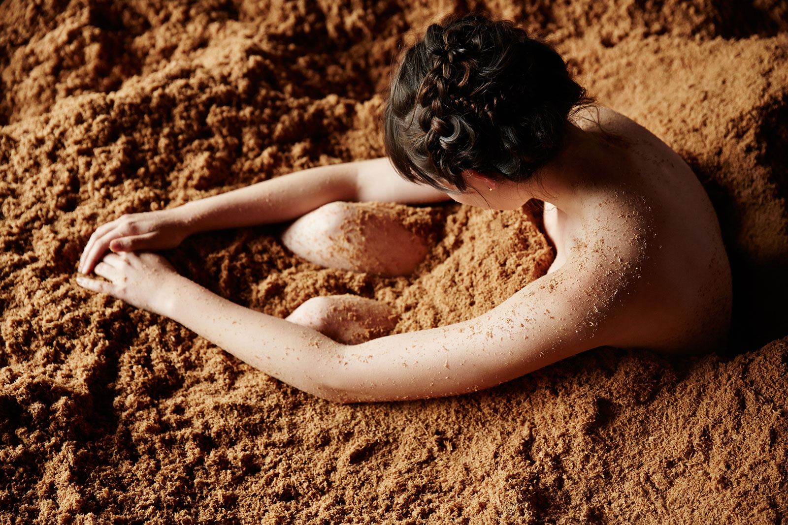 Woman sitting in Japanese Sand Bath at Spa  | Dovis Bird Agency Photography