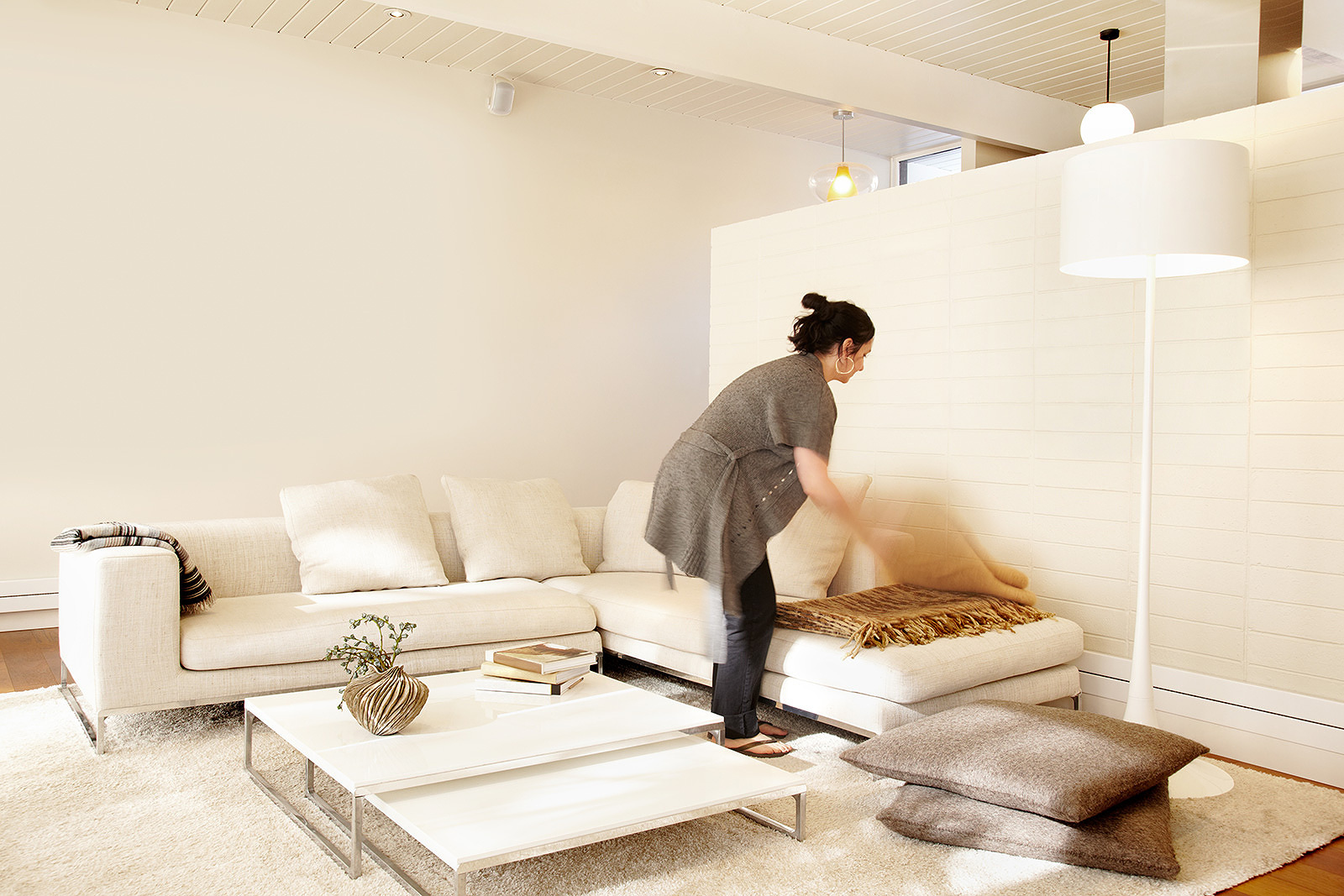 Woman fluffing pillows in living room  | Dovis Bird Agency Photography