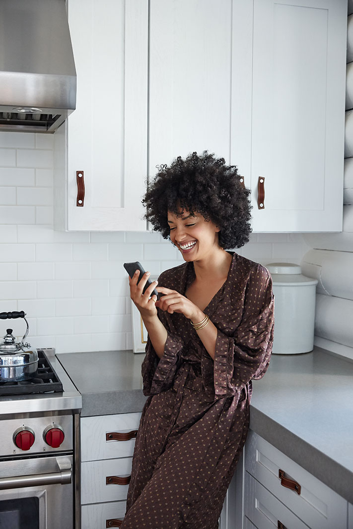 Woman in kitchen on cell phone  | Dovis Bird Agency Photography